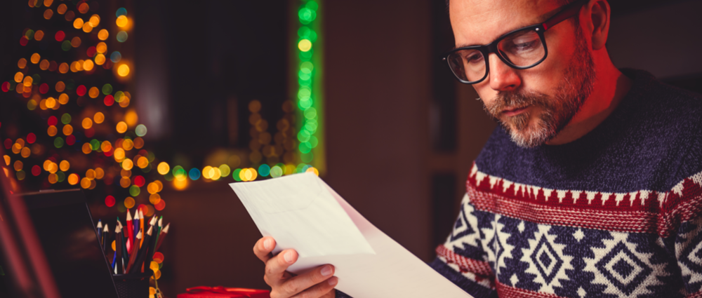 blog around the holidays main image; man in sweater reading a letter with a christmas tree at the background